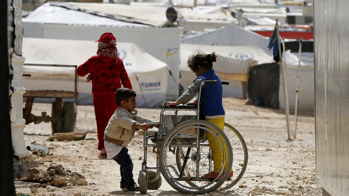 Syrian refugee children play with a wheelchair at the Al Zaatari refugee camp in the Jordanian city of Mafraq, near the border with Syria March 11, 2015. (Reuters)
