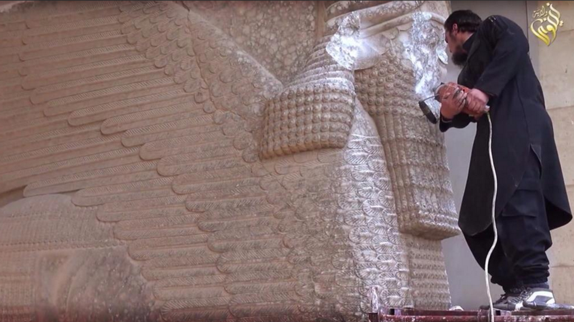 A still from a video showing an ISIS militant using a power tool to deface an Assyrian monument in the ancient city of Hatra, northern Iraq.  (Photo courtesy of Twitter)