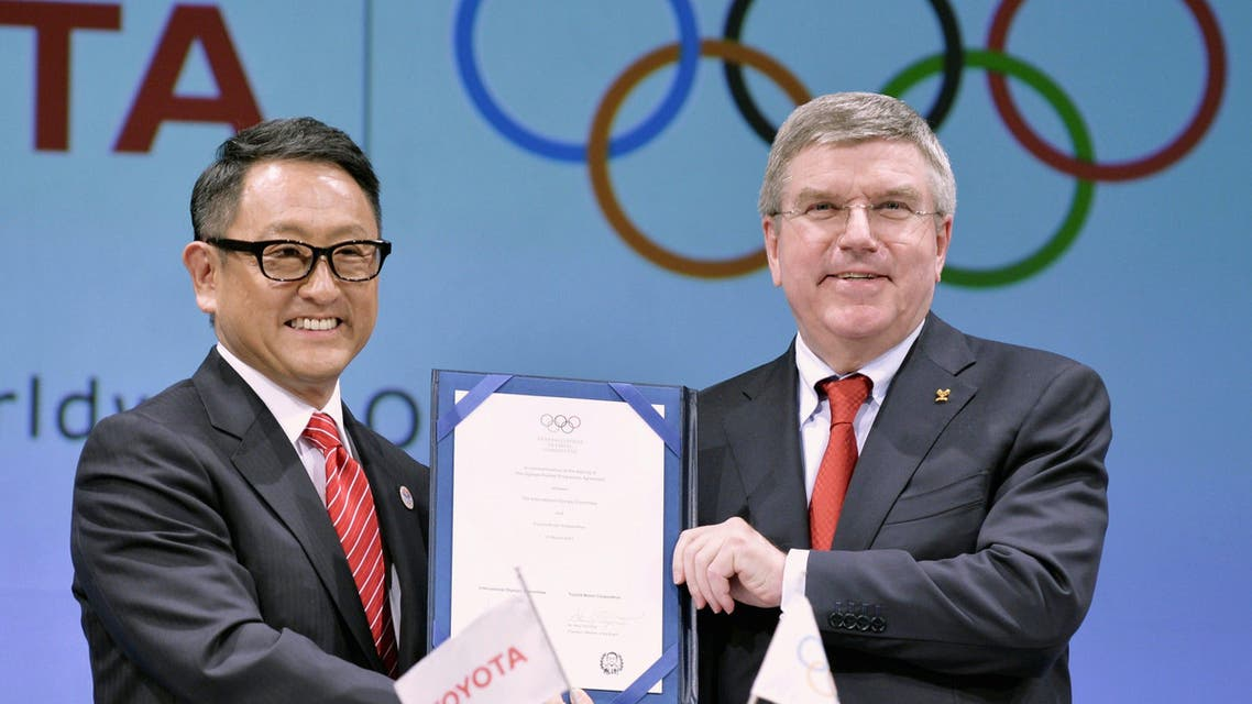 International Olympic Committee (IOC) President Thomas Bach and Toyota Motor Co. President Akio Toyoda hold their agreement document to become part of the IOC's top sponsorship programme (TOP) in Tokyo March 13, 2015. (Reuters)
