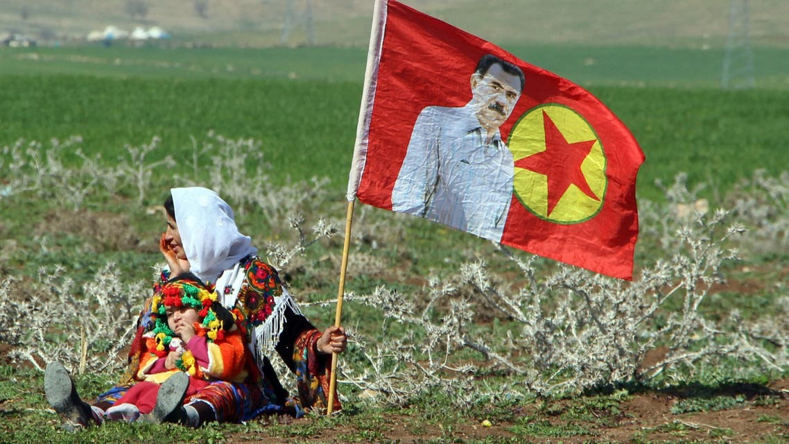 A Turkish Kurdish woman with a child sits next to a PKK flag with a picture of the imprisoned Kurdish rebel leader Abdullah Ocalan during a women's day event in Silopi, in Kurdish dominated southeastern Turkey, March 2, 2015. REUTERS