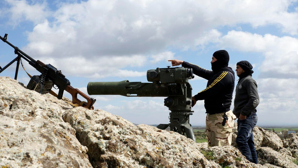 A rebel fighter of the Southern Front of the Free Syrian Army gestures while standing with his fellow fighter near their weapons at the front line in the north-west countryside of Deraa March 3, 2015. (Reuters)