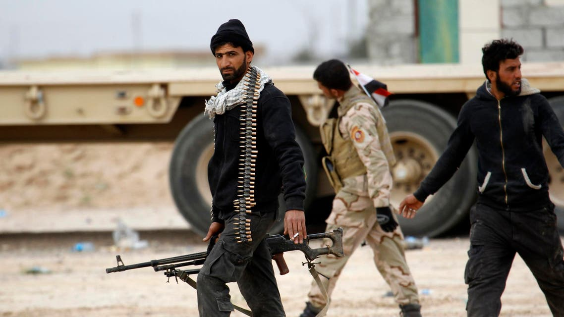 Shi'ite fighters known as Hashid Shaabi walk with their weapons on the southern edge of Tikrit March 12, 2015. (Reuters)