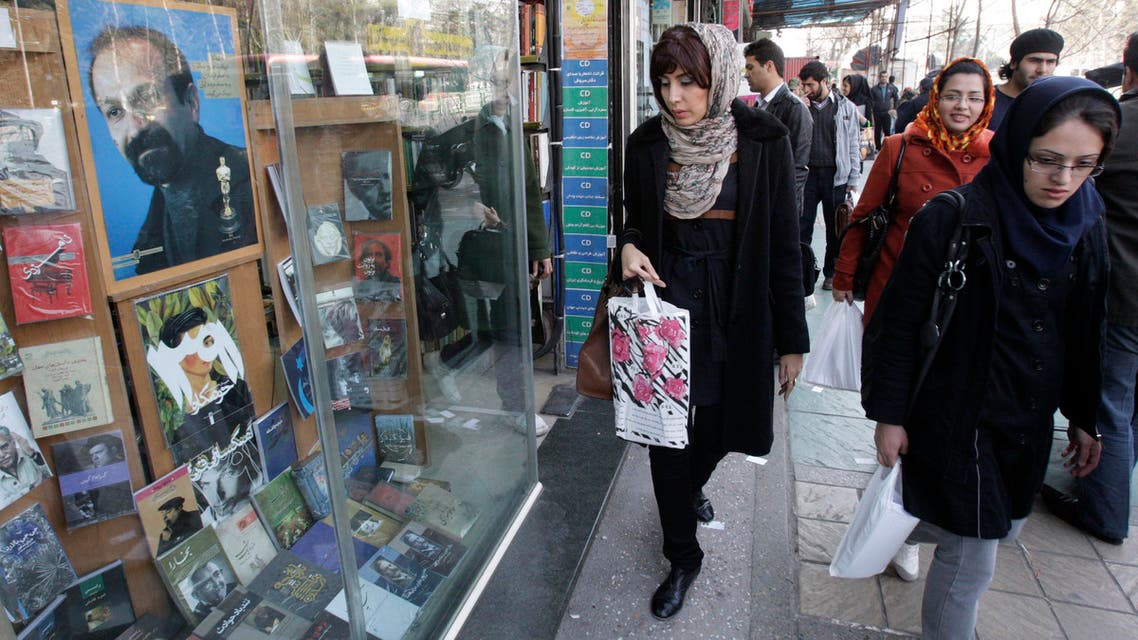 Iranian pedestrians walk past a book shop decorated with a poster of Asghar Farhadi, Iranian Oscar winner filmmaker, in central Tehran, Iran, Tuesday, Feb. 28, 2012. AP