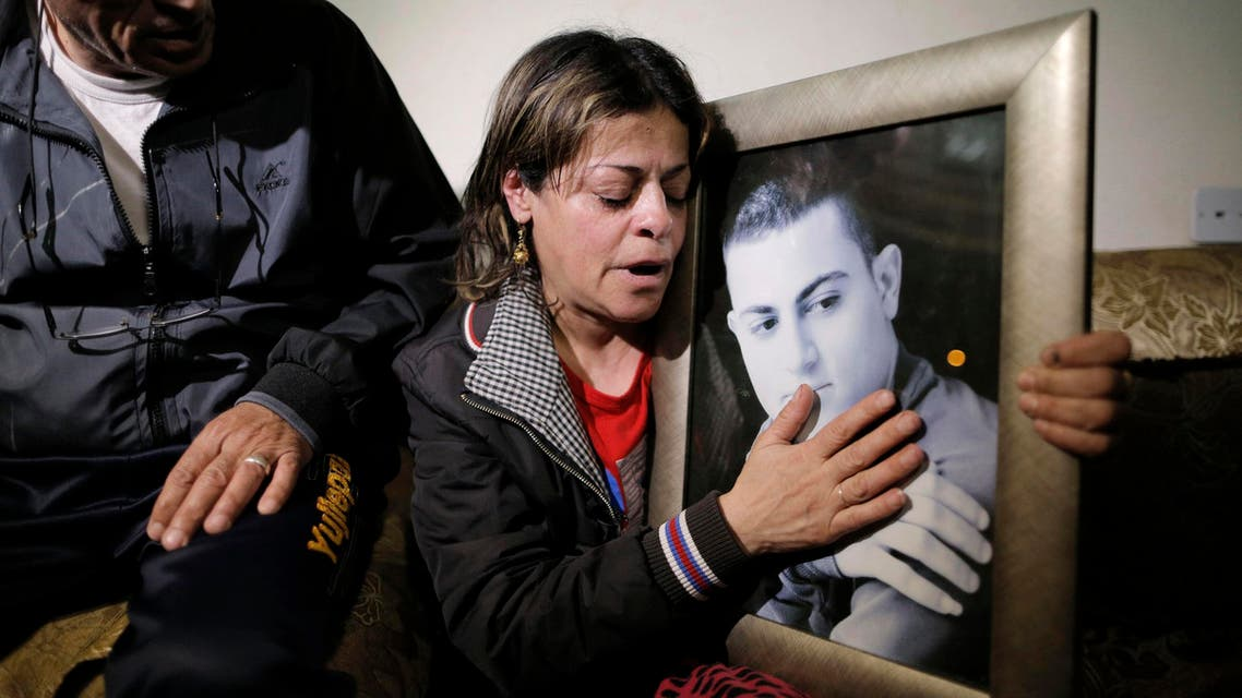 The mother and father of Muhammad Musallam, an Israeli Arab held by Islamic State in Syria as an alleged spy, react beside a picture of him in their East Jerusalem home March 10, 2015. Reuters
