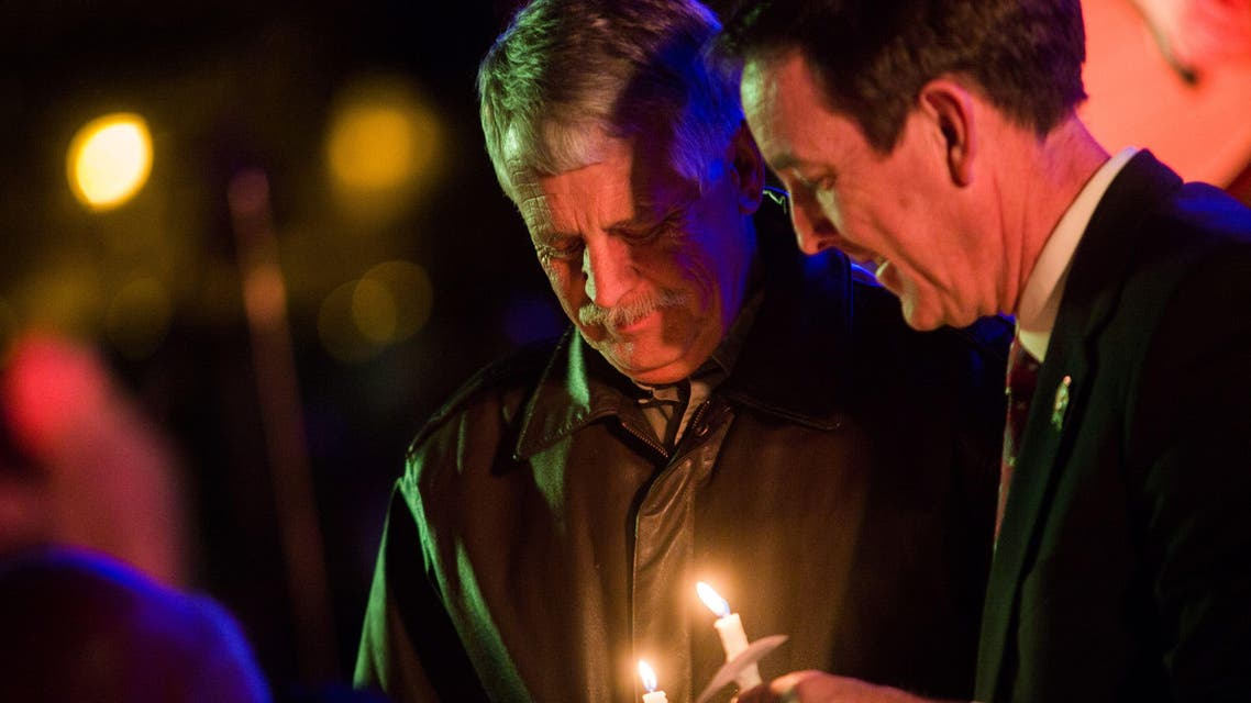 Carl Mueller holds his candle during a candlelight memorial honoring his daughter aid worker Kayla Mueller at the Prescott's Courthouse Square in Prescott, Arizona, February 18, 2015. Reuters