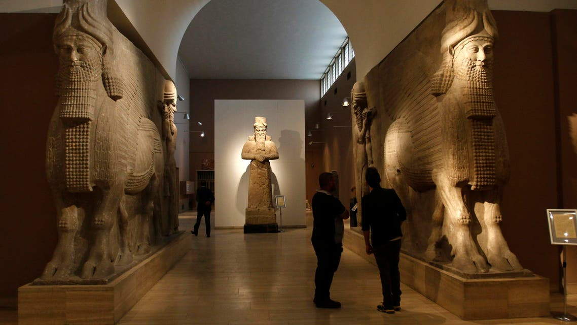 People look at ancient Assyrian human-headed winged bull statues at the Iraqi National Museum in Baghdad March 8, 2015. REUTERS