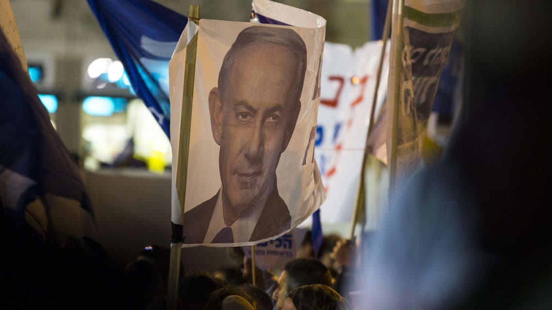 Supporters of Israeli Prime Minister and Likud party's candidate running for general elections, Benjamin Netanyahu, carry posters bearing his portrait during his campaign meeting on March 15, 2015, AFP
