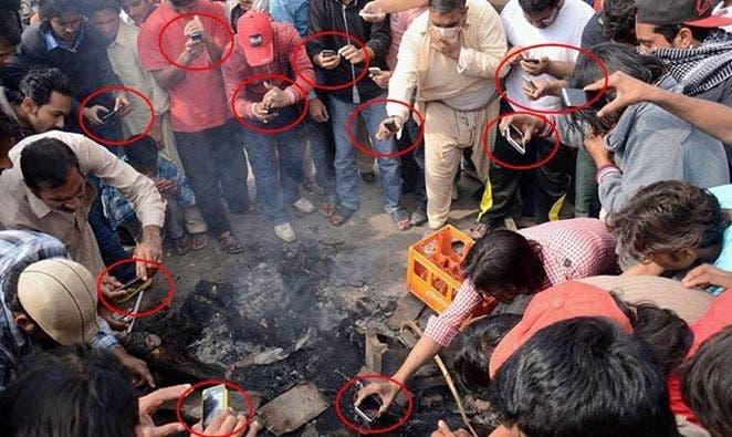 لاہور میں مشتعل مسیحی مظاہرین دونوں افراد کی جلی ہوئی لاشوں کی اپنے موبائل کیمروں سے تصاویر بنا رہے ہیں۔