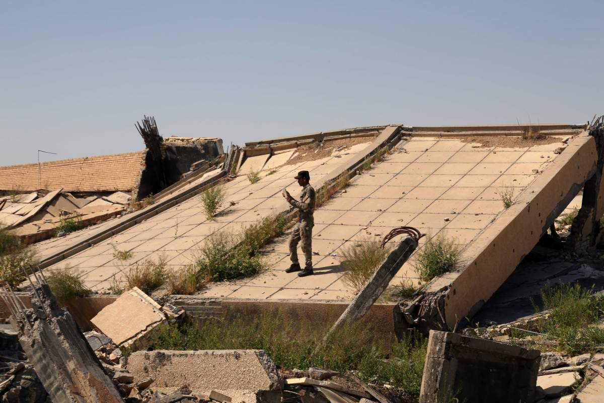 An Iraqi soldier takes photos of the demolished tomb of former Iraqi president, Saddam Hussein, in Tikrit, Iraq, March 15, 2015