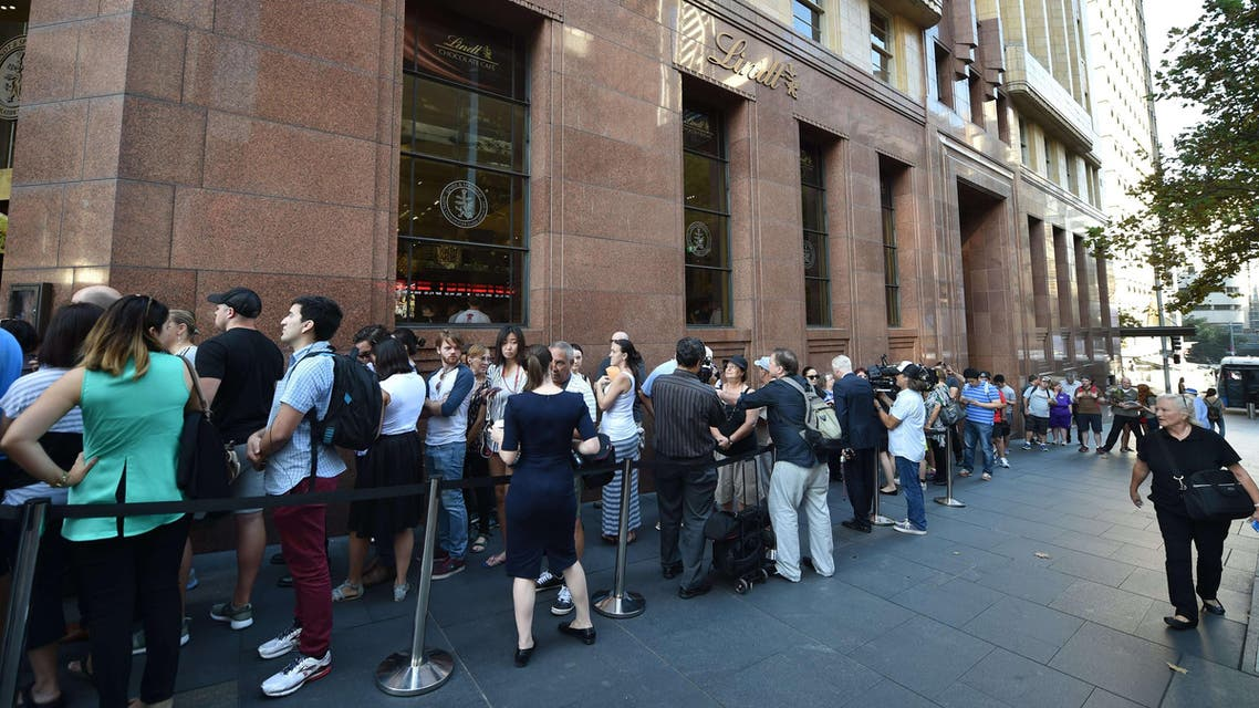 Members of the public queue outside the Lindt Cafe at Martin Place in Sydney ahead of the re-opening on March 20, 2015. AFP