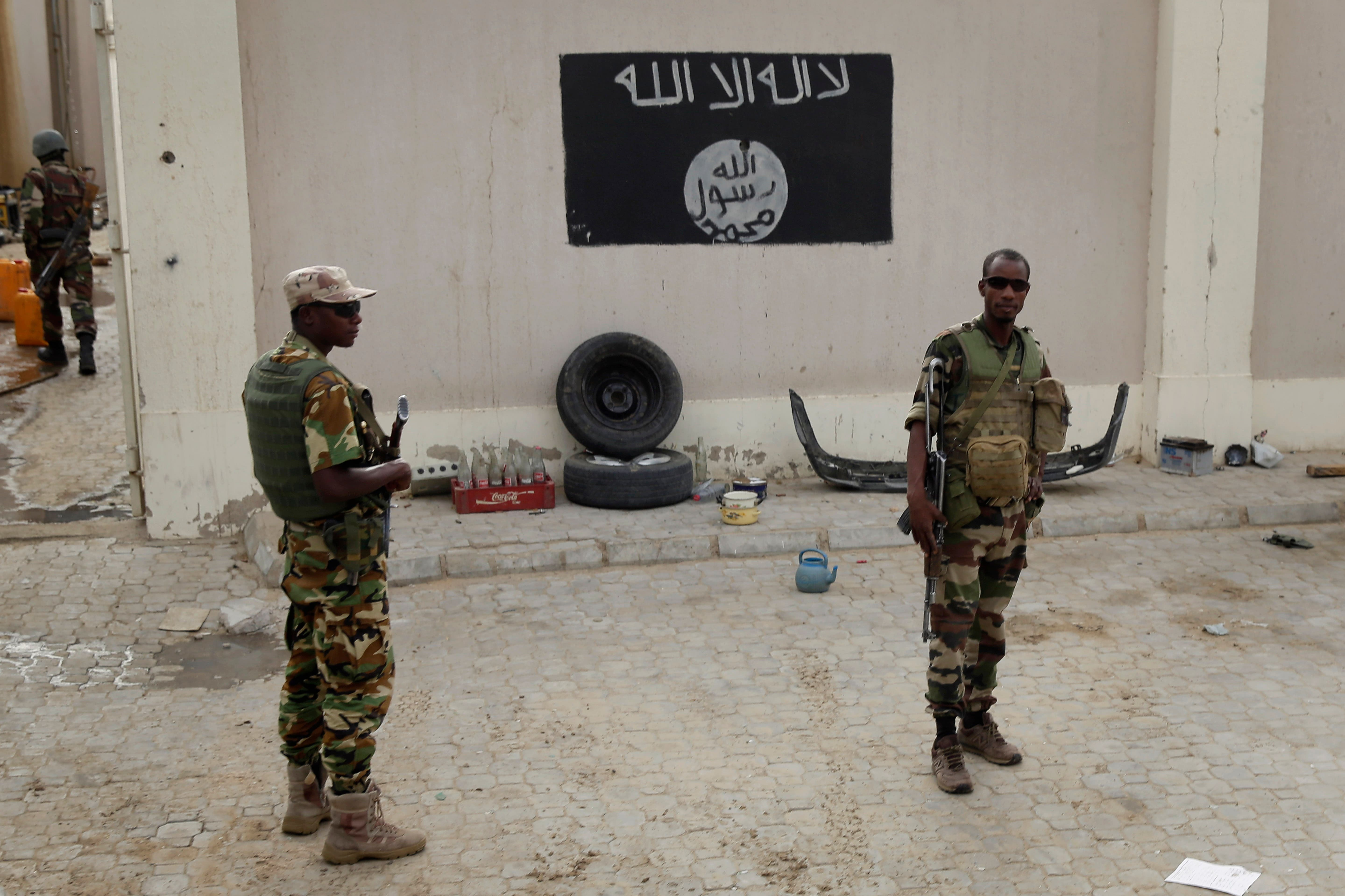 Chadian soldiers stand at a checkpoint in front of a Boko Haram flag the Nigerian city of Damasak, Nigeria, Wednesday March 18, 2015. Damasak was flushed of Boko Haram militants last week, and is now controlled by a joint Chadian and Nigerien force. (AP)