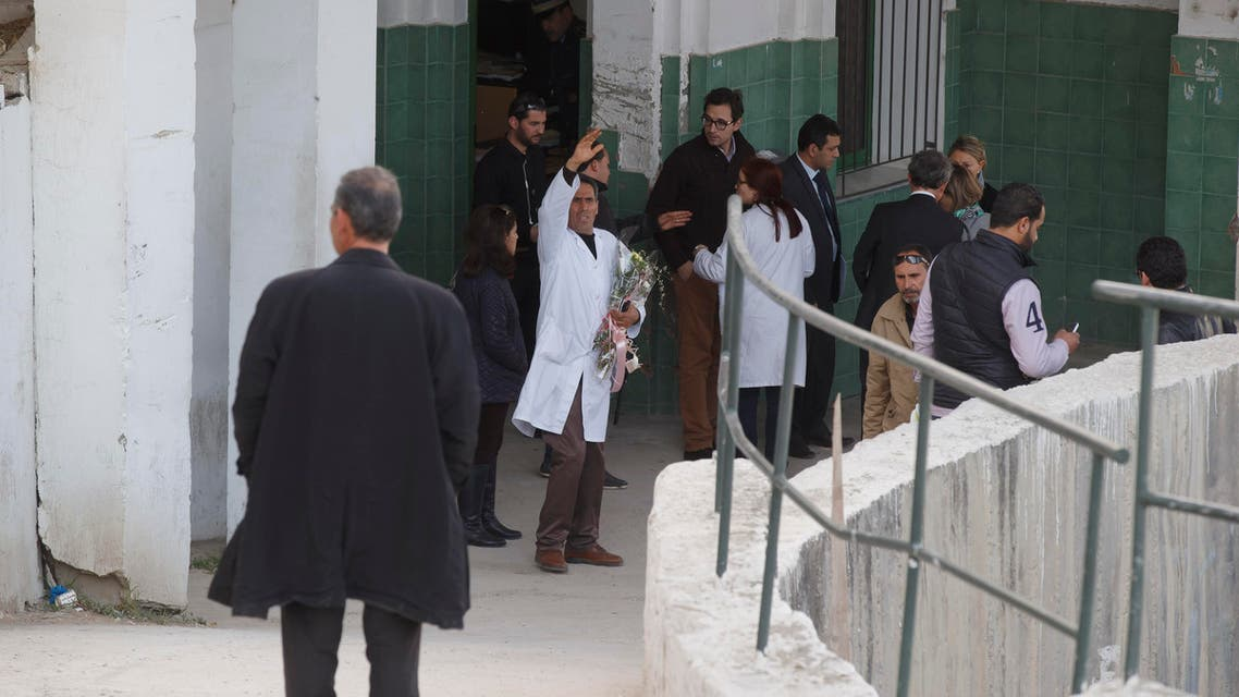 A Tunisian doctor gestures as he holds flowers amongst embassy staff of different countries at the morgue of the Charles Nicolle hospital in Tunis Tunisia, Thursday, March 19, 2015. (AP)
