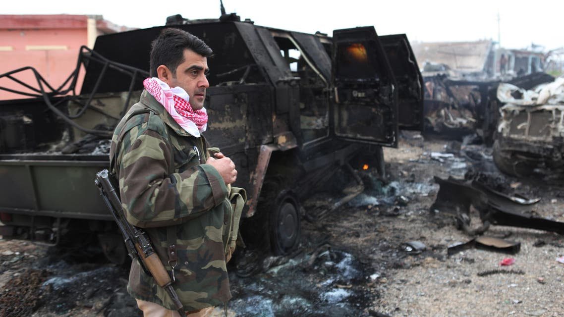 A member of the Kurdish forces stands next to an armored vehicle destroyed by an improvised explosive device placed by Islamic State militants that killed several Peshmerga fighters and injured dozens late Wednesday, when they pushed towards Sinjar Mountain, as they inspect the aftermath of the site in Kasr Reej, Iraq, Thursday, Dec. 18, 2014. AP