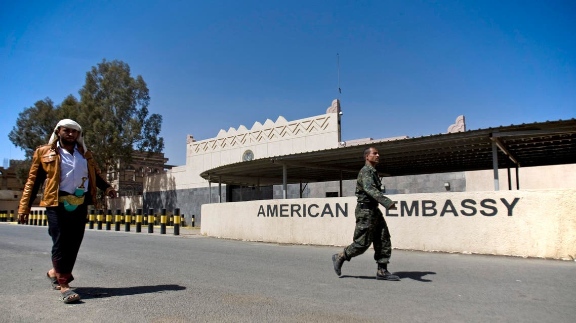Houthi Yemenis walk past the gate of the main entrance of the closed U.S. embassy after Yemeni police opened the road in front of it, in Sanaa, Yemen, Wednesday, March 4, 2015. AP