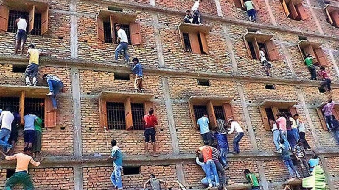 In this Wednesday, March 18, 2015 file photo, Indians climb the wall of a building to help students appearing in an examination in Hajipur, in the eastern Indian state of Bihar. (AP)