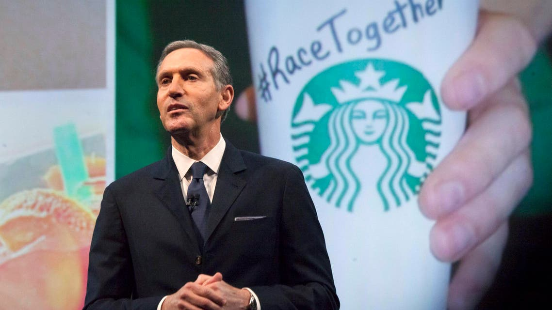 """Starbucks Corp Chief Executive Howard Schultz, pictured with images from the company's new """"Race Together"""" project behind him, speaks during the company's annual shareholder's meeting in Seattle, Washington March 18, 2015. (Reuters)"""
