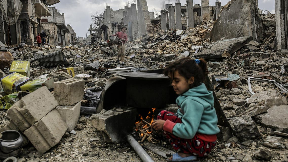 Kurdish Syrian girls are pictured among destroyed buildings in the Syrian Kurdish town of Kobane, also known as Ain al-Arab, on March 22, 2015. AFP