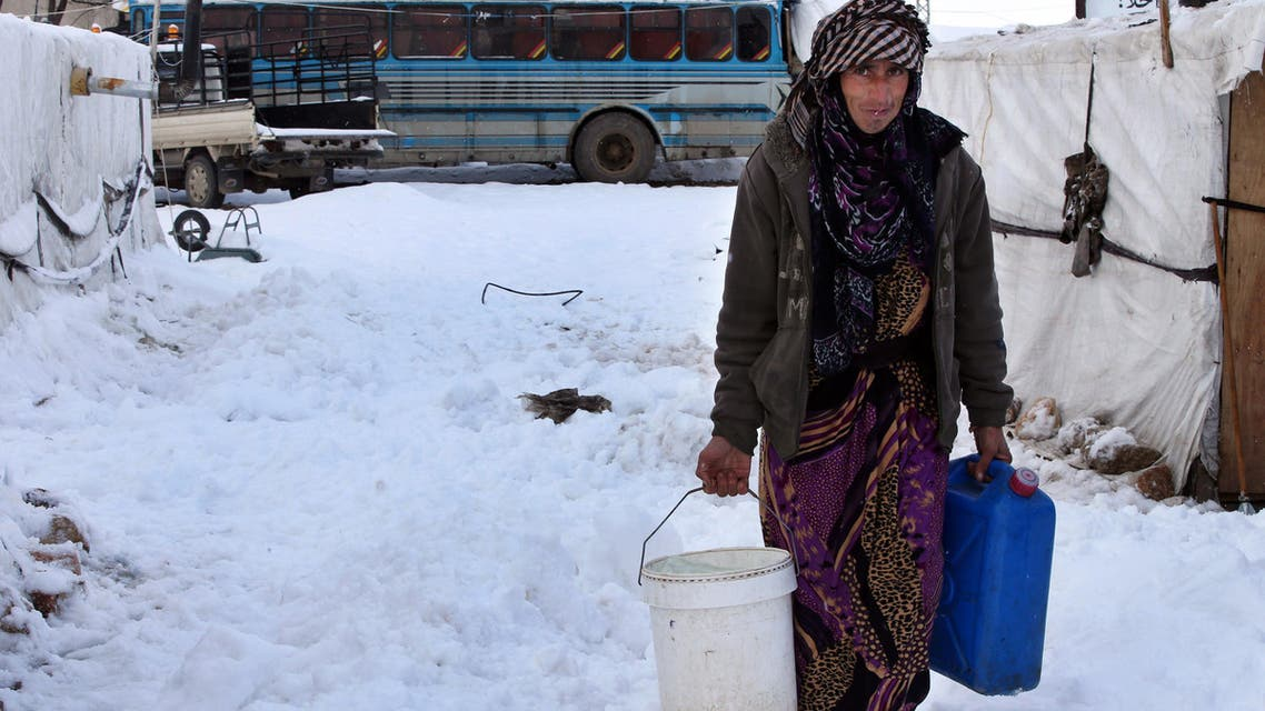 A Syrian woman carries water as she walks through snow at a refugee camp in al-Majdal village, Bekaa valley, east Lebanon, Thursday, Jan. 8, 2015. (AP)