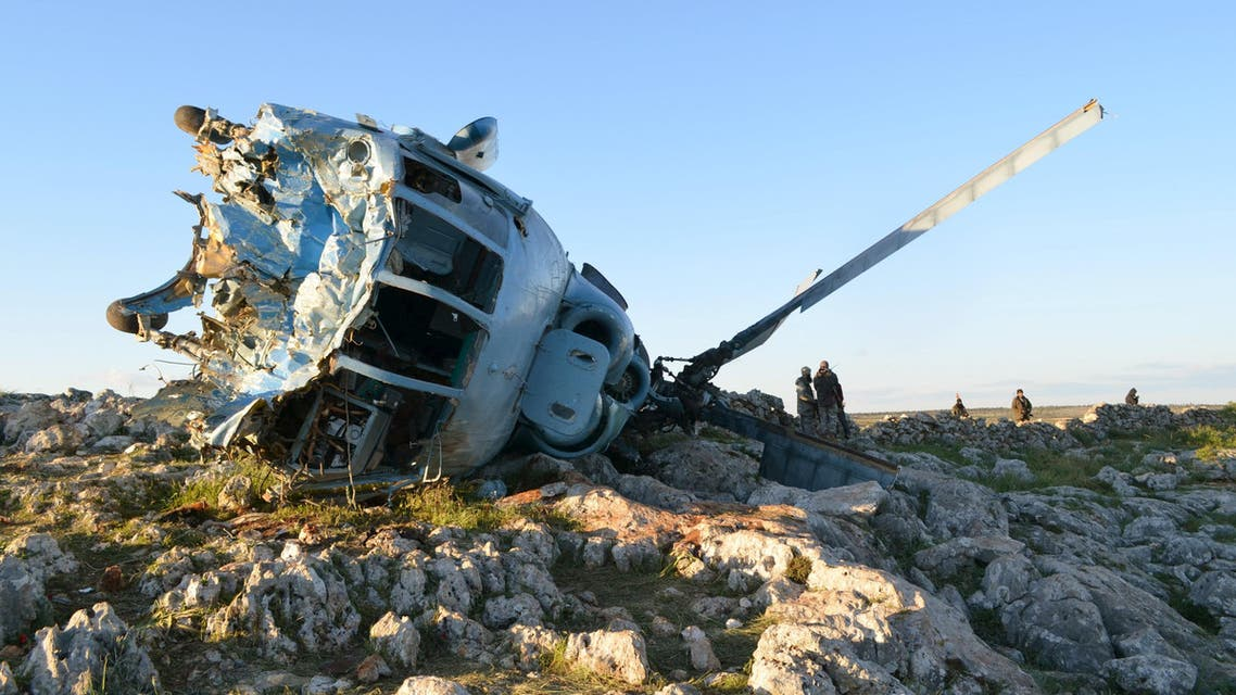 Nusra Front fighters inspect a helicopter that belongs to forces loyal to Syria's President Bashar Al-Assad after it crashed in Jabal al-Zawiya in the southern countryside of Idlib March 22, 2015.  (Reuters)