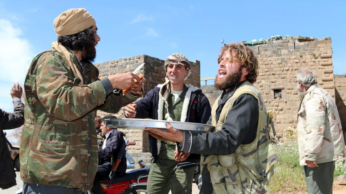 Rebel fighters distribute sweets in celebration in front Bosra's ancient citadel in the historic Syrian southern town of Bosra al-Sham, after they took control of the area, March 25, 2015. (Reuters)