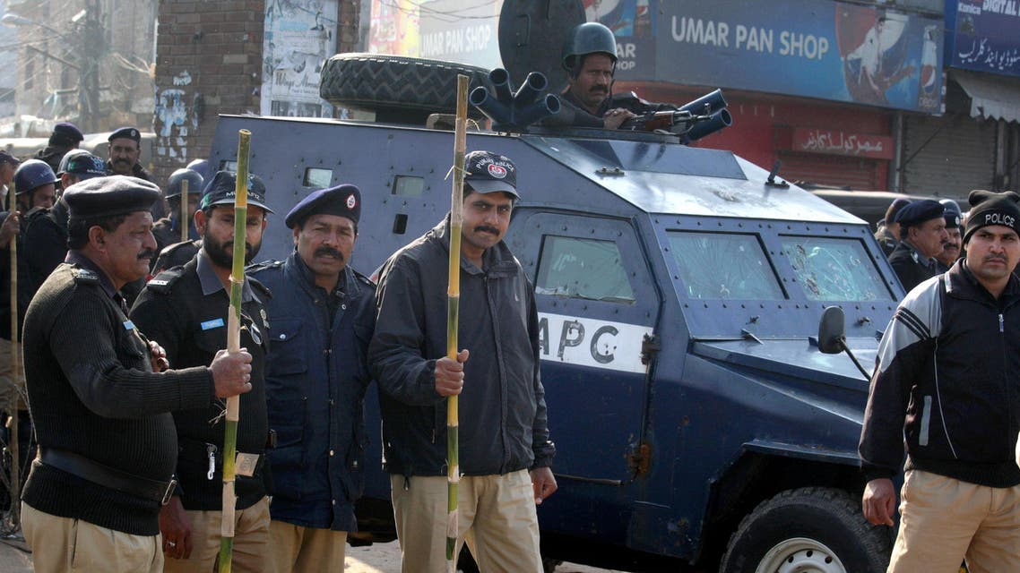 Pakistani police officers stand guard close to the venue of a mass funeral service of the victims of Sunday's pair of suicide attacks on two churches in Lahore, Pakistan, Tuesday, March 17, 2015. (AP