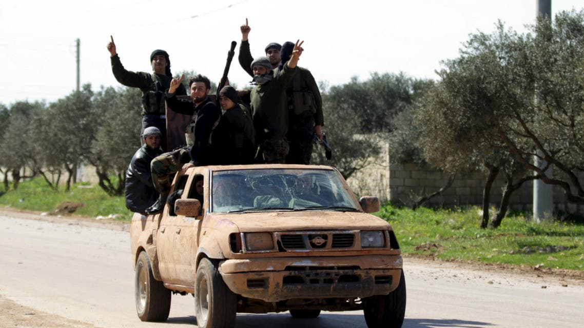 Ahrar al-Sham Islamic Movement rebel fighters ride on the back of a pick-up truck in the northwestern city of Idlib March 26, 2015. Reuters