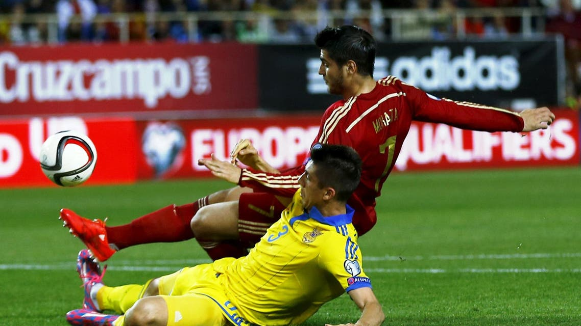 Spain's Alvaro Morata (top) kicks the ball to score next to Ukraine's Yevhen Khacheridi during their Euro 2016 qualifier soccer match at Ramon Sanchez Pizjuan stadium in Seville, March 27, 2015.  (Reuters)