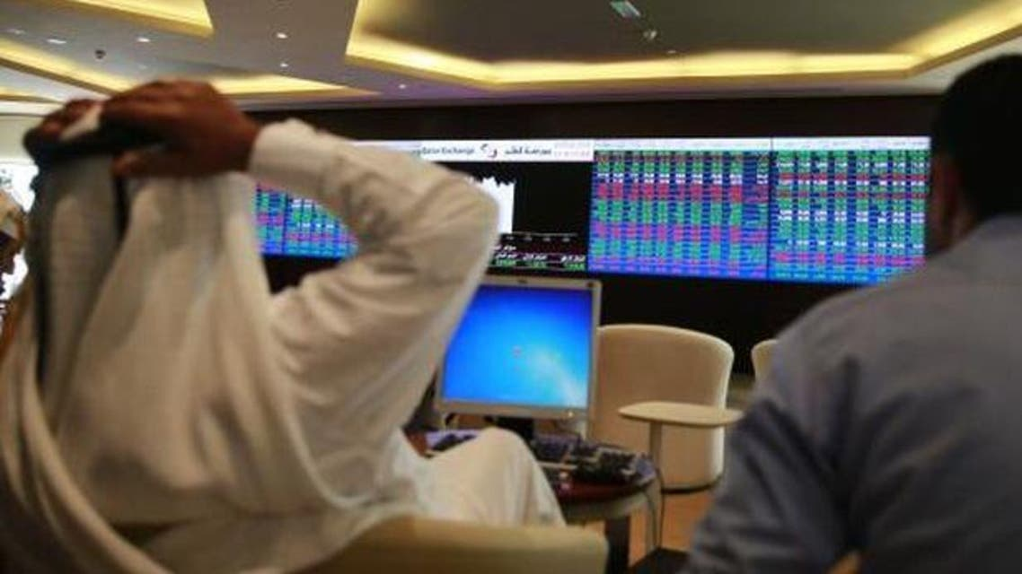 Traders speak with each other as they sit behind their desks in front of the Qatar stock exchange board, in Doha on February 4, 2014.  (Reuters)