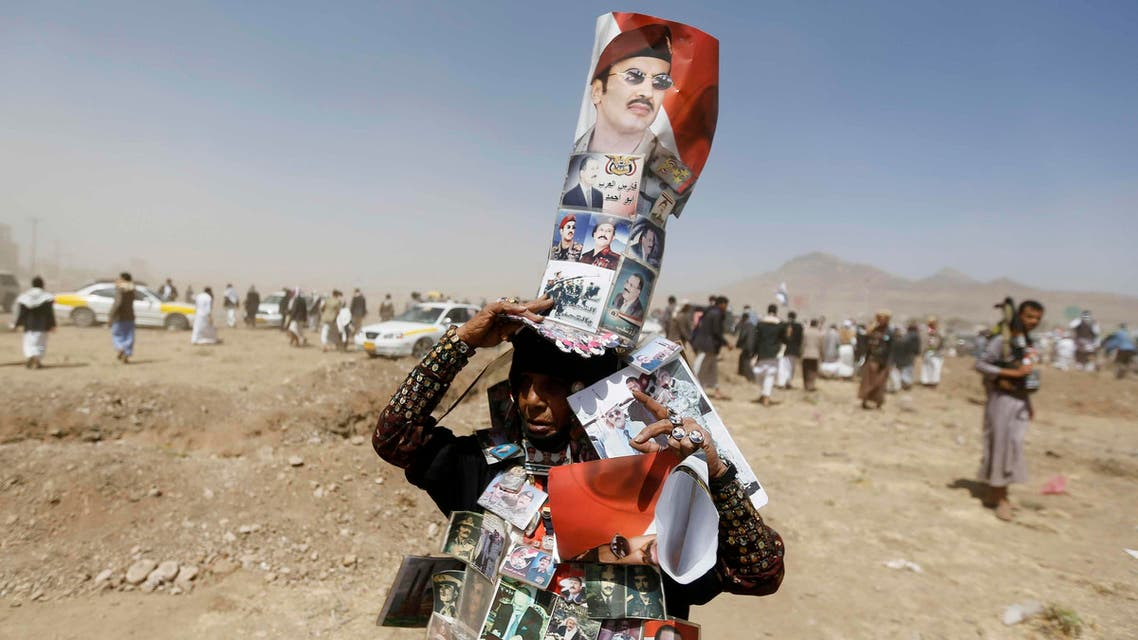 A woman supporting Ahmed Ali Abdullah Saleh, the son of Yemen's former President Ali Abdullah Saleh, wears posters of the Salehs at site of a demonstration demanding for a presidential election to be held and for Ahmed to run for presidency, in Sanaa, March 13, 2015.