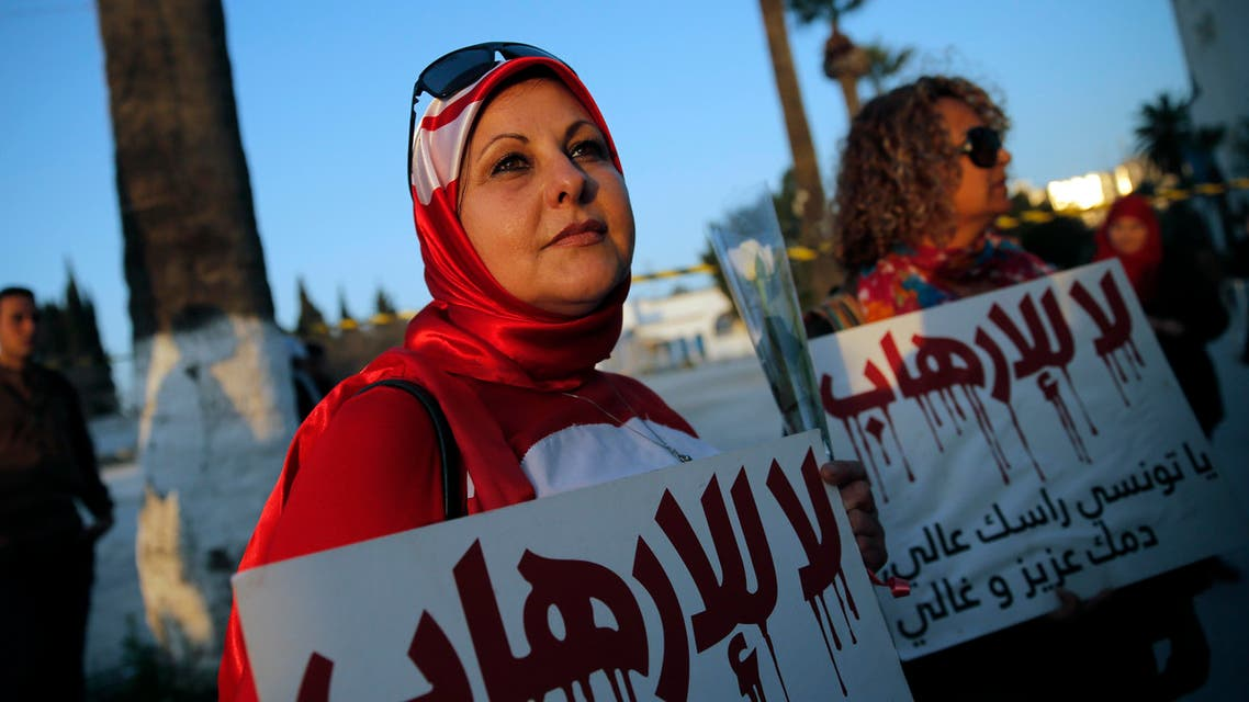 "A woman holds a placard reading: ""No to Terrorism"" as she demonstrates in front of the National Bardo Museum a day after gunmen attacked the museum and killed scores of people in Tunis, Tunisia, Thursday, March 19, 2015.  (AP)"
