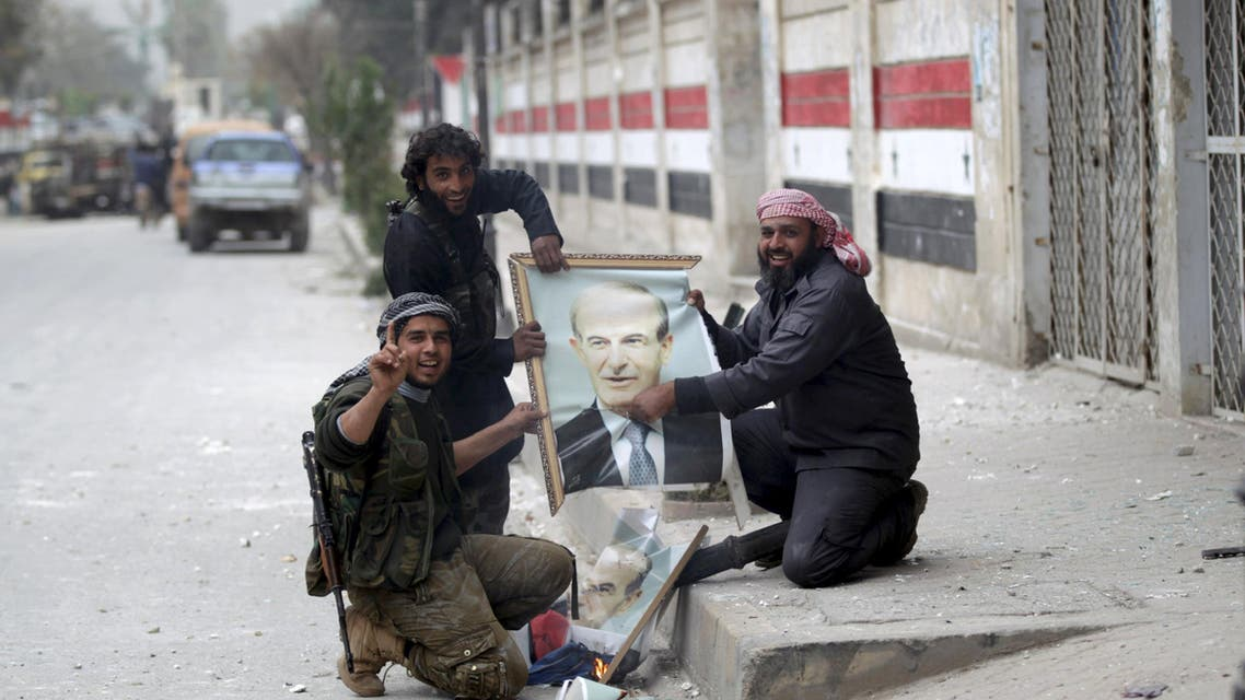 Rebel fighters gesture as they damage a picture of late Syrian president Hafez al-Assad, father of Syrian President Bashar al-Assad, in Idlib city, after they took control of the area March 28, 2015. (Reuters)