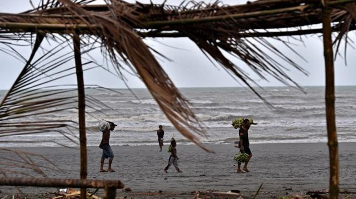 A family carry food supplies on the beach of Kerema, Papua New Guinea. (AFP/Aris Messinis)