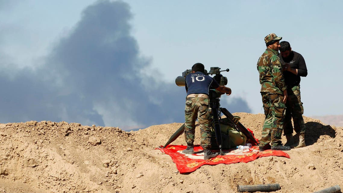 Smoke rises from the Ajil oil field as Shi'ite fighters gather in Al Hadidiya, south of Tikrit, en route to the Islamic State-controlled al-Alam town, where they are preparing to launch an offensive on Saturday, March 6, 2015. (Reuters)