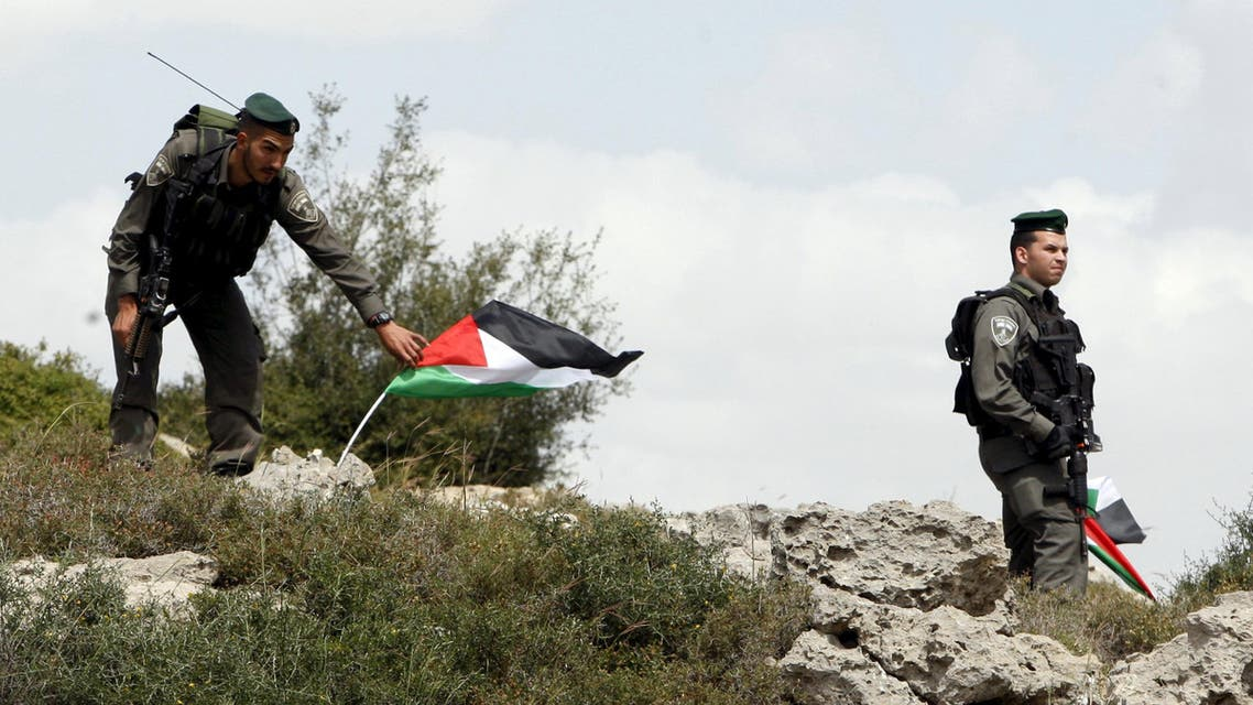 Israeli border policeman remove Palestinian flags during a demonstration by Palestinians marking Land Day and against Jewish settlements in Wadi Foukeen near the West Bank city of Bethlehem March 30, 2015.  (Reuters)