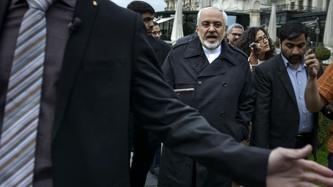 Iranian Foreign Minister Javad Zarif talks to members of the media while walking through a courtyard at the Beau Rivage Palace Hotel during an extended round of talks, Wednesday, April 1, 2015 in Lausanne, Switzerland. (AP)
