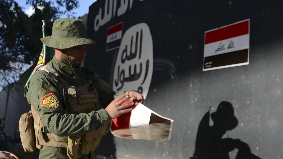 A Shi'ite paramilitary fighter puts Iraqi flags on a wall painted with the black flag commonly used by Islamic State militants in Tikrit March 31, 2015. (Reuters)