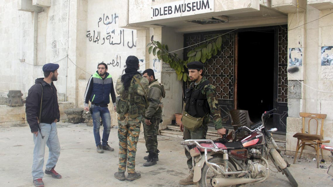 Rebel fighters stand outside Idlib museum in Idlib city, after Islamist rebel fighters took control of the area April 1, 2015. (Reuters)