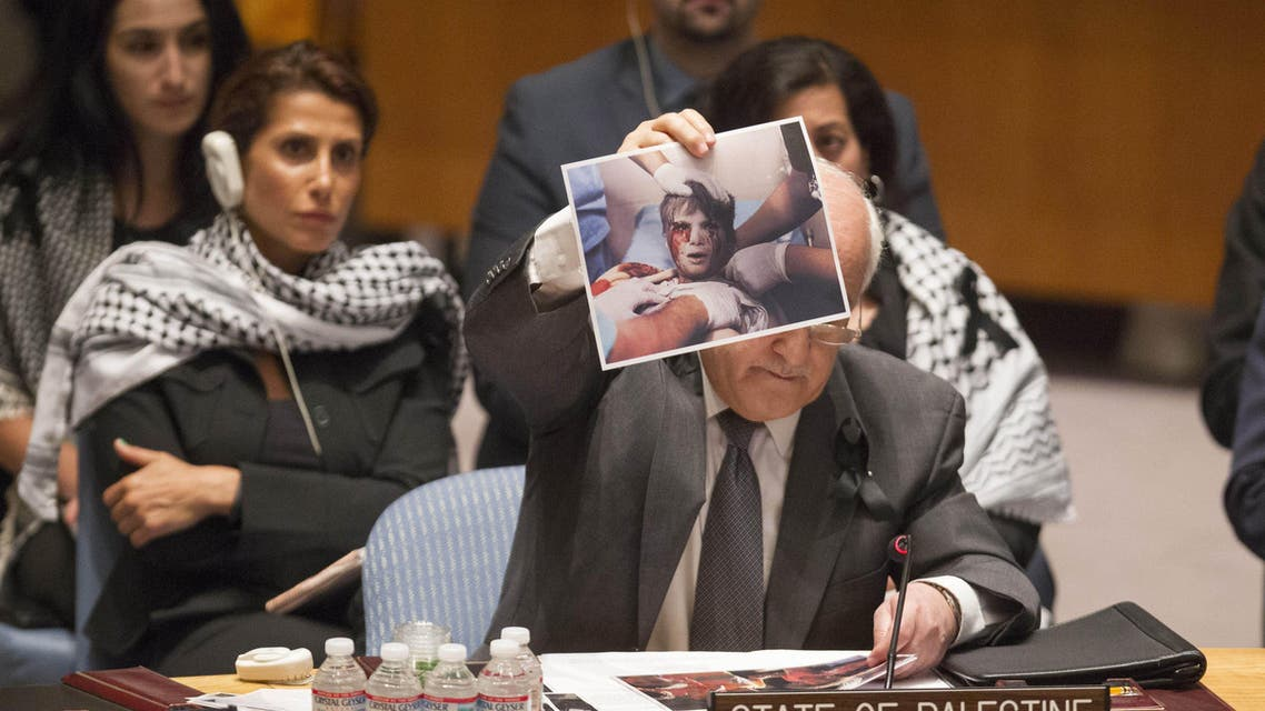Riyad H. Mansour, Permanent Observer of the State of Palestine to the UN, holds up a photo from the fighting between Israelis and Hamas militants who control the Gaza Strip, as he addresses the Security Council at the United Nations in New York, Tuesday, July 22, 2014. (File Photo:AP)