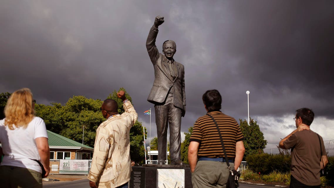 A tour guide, second left, speaks to French tourists as he, mimics the statue of former South African President Nelson Mandela with a raised fist outside the former Victor Verster prison, renamed to Drakenstein Correctional center near the town of Franschhoek, South Africa, Tuesday, Feb. 10, 2015. (AP)