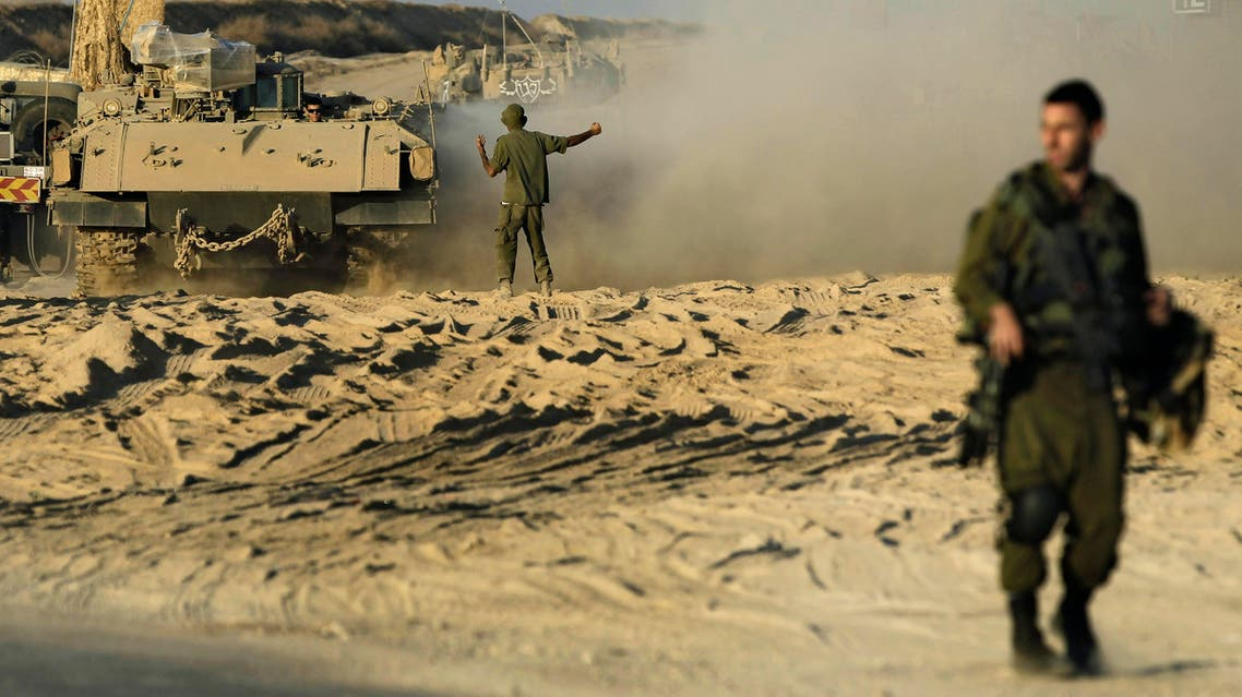 An Israeli solider directs an Armored Personnel Carrier (APC) near the border between Israel and Gaza, Monday, Oct. 28, 2013. (AP)
