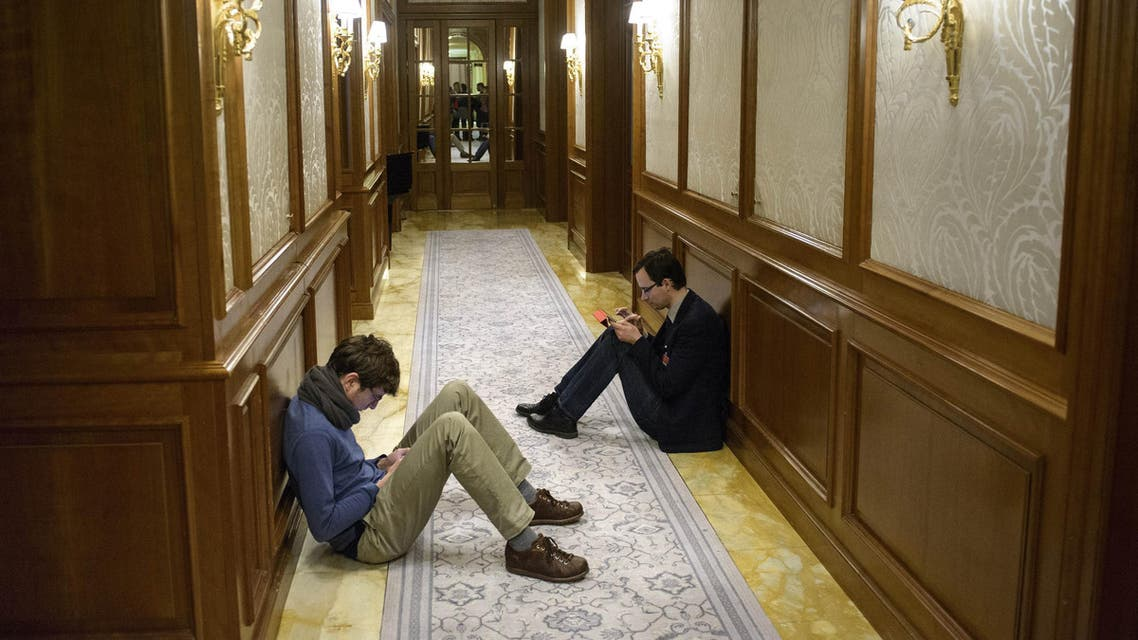 Reporters sit in a hallway during the Iran nuclear program negotiations at the Beau Rivage Palace Hotel in Lausanne, Switzerland, Wednesday, April 1, 2015. (AP)