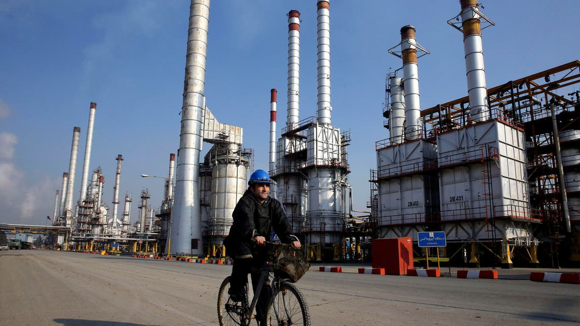 In this Monday, Dec. 22, 2014 photo, an Iranian oil worker rides his bicycle at the Tehran's oil refinery south of the capital Tehran, Iran. (AP)