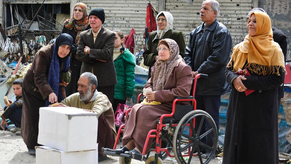Residents wait to receive humanitarian aid at the Palestinian refugee camp of Yarmouk, in Damascus March 11, 2015. (Reuters)