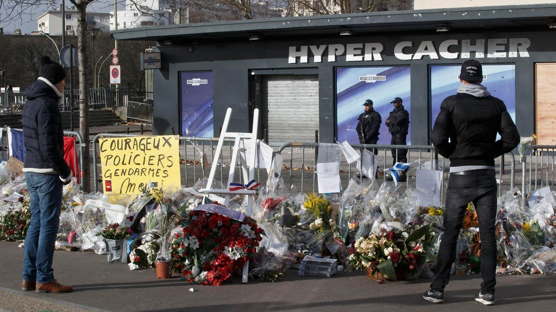 People look at flowers laid outside the kosher grocery store in Paris, Sunday Feb. 8, 2015, where four people where killed in a terror attack. (AP)