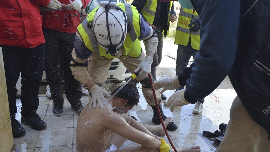 Civil Defense members spray water on a rebel fighter, affected by what activists said was a gas attack, in Idlib city March 31, 2015. (Reuters)