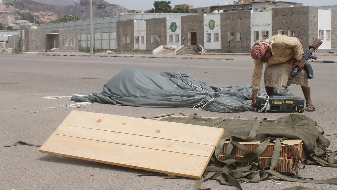 An armed Yemeni  man inspects a box attached to a parachute, reportedly air-dropped by the Saudi-led coalition, at the special forces camp on April 3, 2015 in Aden. (AFP)