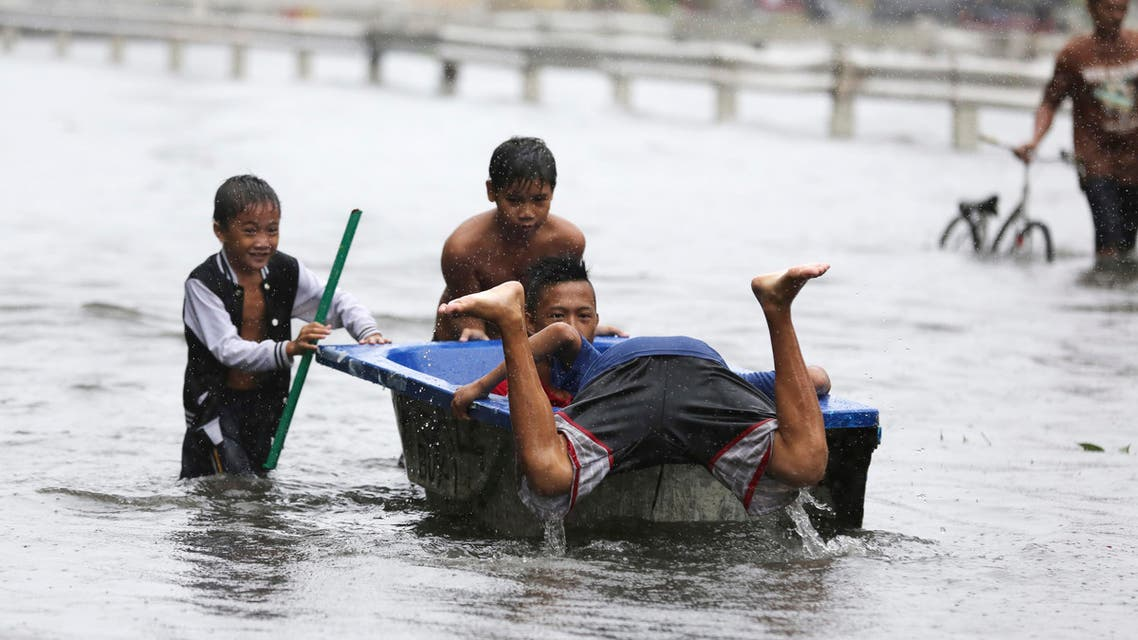 Filipino children play with a bathtub along flooded roads as Typhoon Rammasun batters suburban Navotas, Philippines on, July 16, 2014. (AP)