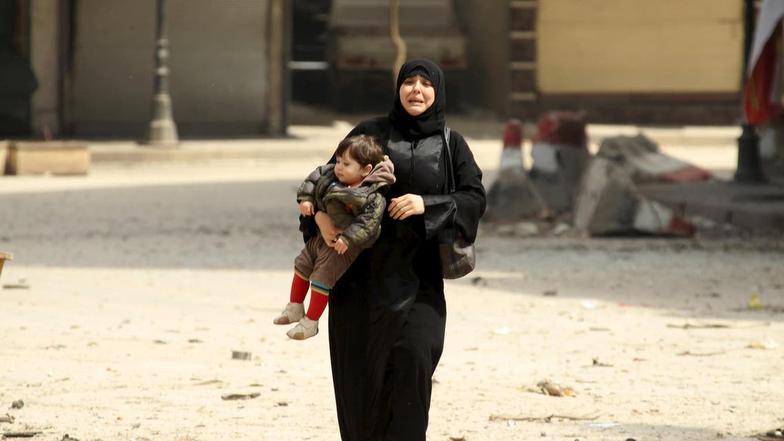 A woman carrying a child reacts at a damaged site after what activists said was shelling by forces loyal to Syria's president Bashar al-Assad on a mosque in Idlib city, after rebels took control of the area April 3, 2015. Reuters