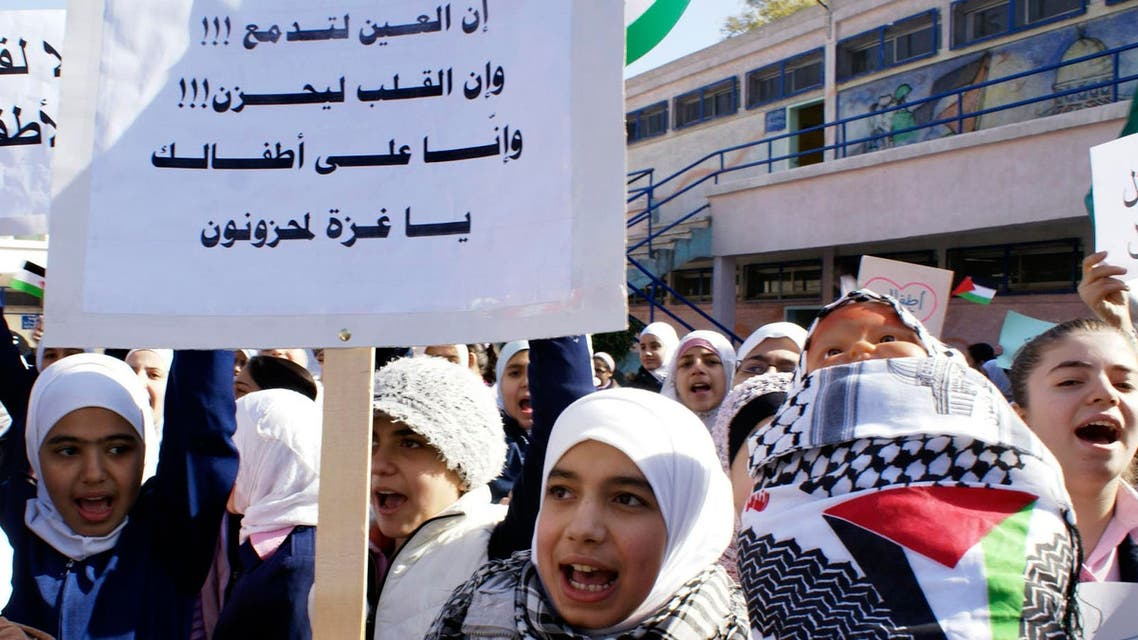 """A Palestinian student shouts slogans as she carries a banner in Arabic that reads :"""" The eye is crying, the heart is sad, and we are mourning on your children Gaza,"""" at the Yarmuk Palestinian refugee camp in Damascus, Syria. (File: AP)"""