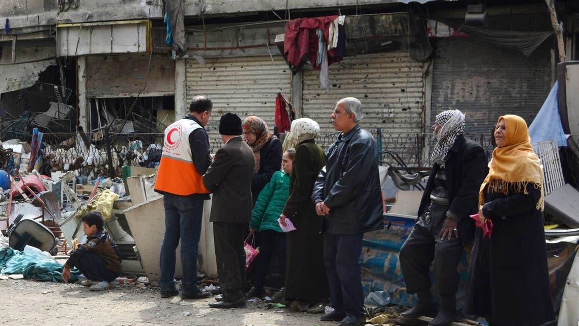سكان من مخيم اليرموك ينتظرون لاستلام مساعدات إنسانية